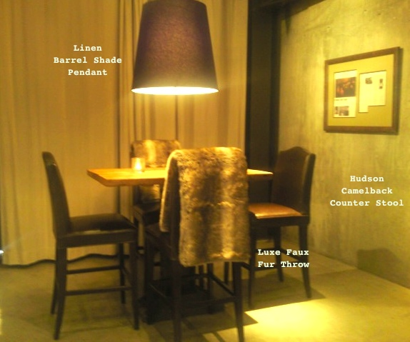 A barrel pendant lamp casts a soft glow over a table ringed by leather counter chairs draped in faux fur throws.